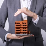 business person holds apartment building miniature model