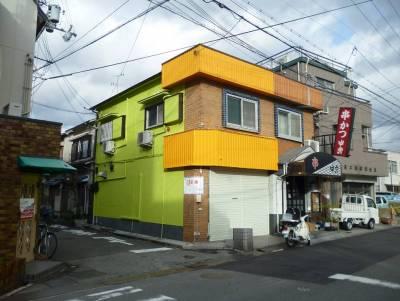 角地でオレンジ色とライムグリーン色の分かり易い建物です。